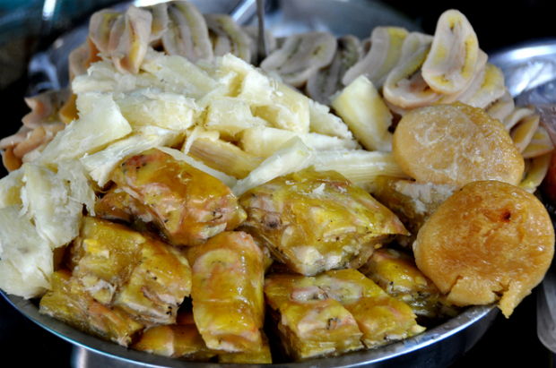 Steamed banana and cassava are chopped into bite-sized pieces, ready to be covered in coconut milk.