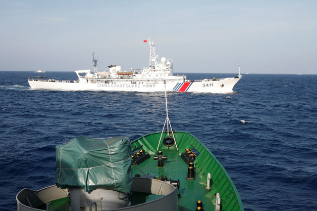A ship (top) of the Chinese Coast Guard is seen near a ship of the Vietnam Marine Guard in the Vietnams East Sea, about 210 km (130 miles) off shore of Vietnam May 14, 2014. Photo by Reuters/Nguyen Minh