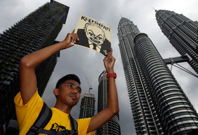 A man holds up a poster as pro-democracy group Bersih stages a 1MDB protest, calling for Malaysian Prime Minister Najib Abdul Razak to resign, in Kuala Lumpur, Malaysia November 19, 2016. Photo by Reuters/Edgar Su