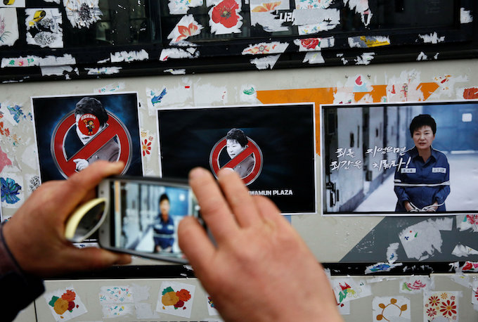 A man takes a picture of stickers showing computerized images of South Korean President Park Geun-hye which are attached to a police bus by protesters, during a protest calling for Park to step down in Seoul, South Korea, November 26, 2016. Photo by Reuters/Kim Kyung-Hoon