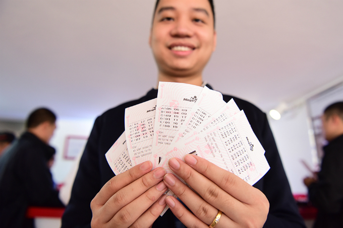 A man is showing 6 tickets he bought.