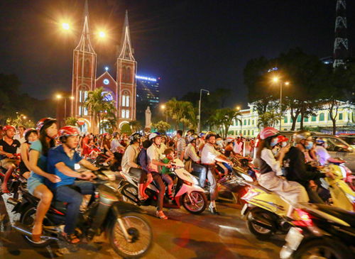 Several people with their vehicles near the Saigon Notre Dame Cathedral in District 1