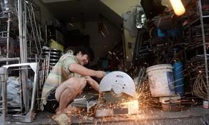 On Hanoi's blacksmith street a lone forge burns bright