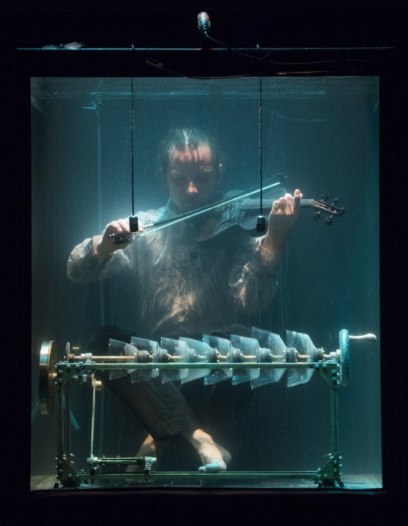 A member of the Between Music band, performs with a custom-made instrument in a glass water tank during the AquaSonic underwater concert. Photo by AFP/Jonathan Nackstrand
