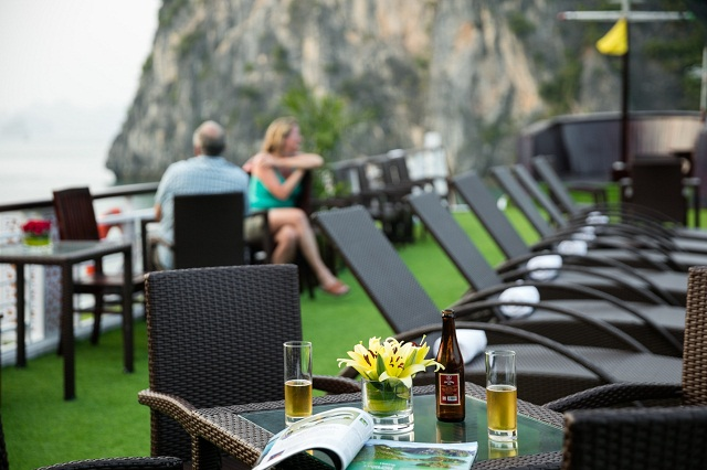 Visitors can sit on the sundeck of Paloma Cruise and enjoy a glass of wine or cocktail for panoramic views of Halong Bay.
