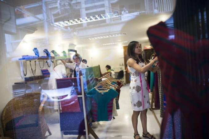 boutique owner Pyone Thet Thet Kyaw (R), owner and designer of Virya Couture, checking the clothes in her shop at Yangon. Photo by AFP/Ye Aung Thu