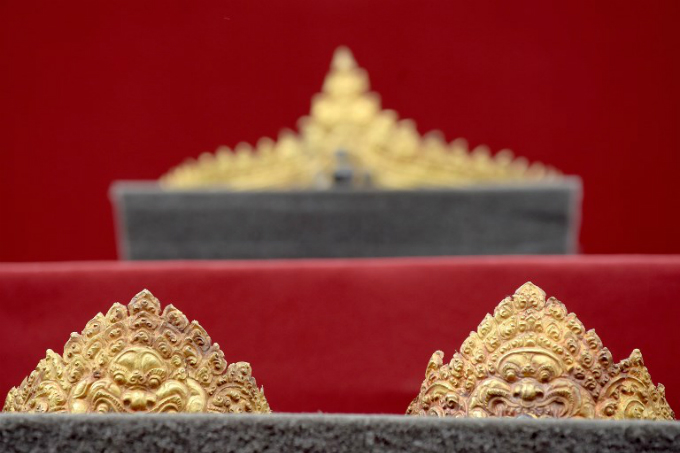 A set of returned Angkorian-era gold jewellery is displayed to the public behind protective glass during a ceremony in front of the National Museum upon its arrival in Phnom Penh on December 2, 2017. Photo by AFP/Tang Chhin Sothy