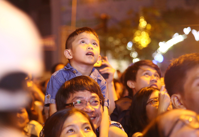 A boy sits on his fathers shoulders as the family watches the fireworks show.