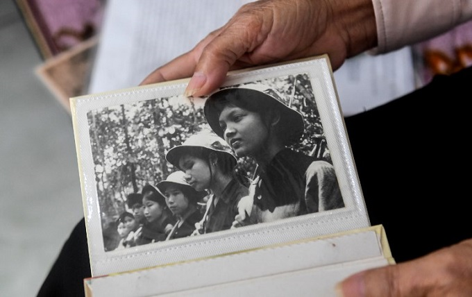 Hoang Thi No, who was a member of the Perfurme River squad - a top secret female combat unit formed in 1967, shows a photograph of squad members in Vietcong uniform during an interview with AFP at her home in Hue. Photo by AFP/Hoang Dinh Nam