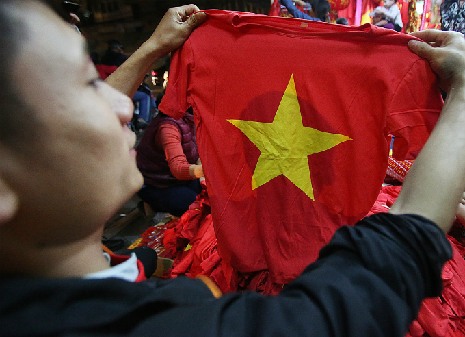A flag T-shirt is sold for VND80,000 each, and VND650,000 for 10 of them. Red is the official color of the Vietnamese team.