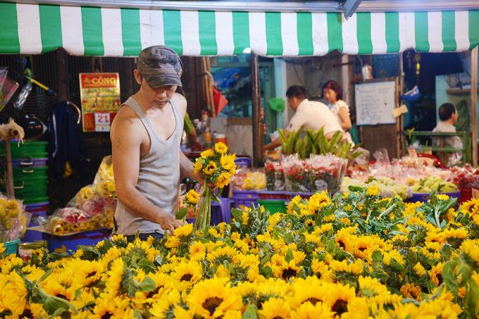 A man picks a bunch of sunflowers at Ho Thi Ky Market in Saigon. Photo by VnExpress/Phong Vinh