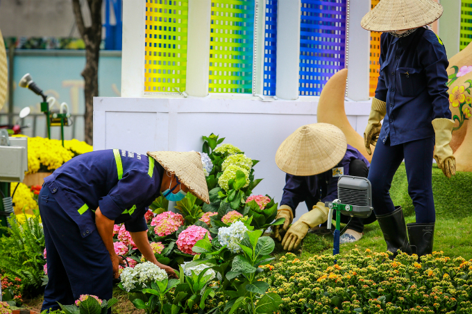 Workers, with their non la, the palm-leaf conical hat of Vietnam, are finishing their last steps to make the flower street look best.