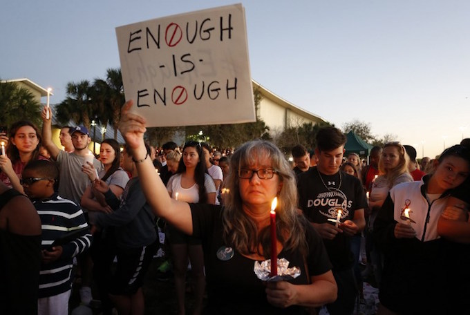 Mourners stand during a candlelight vigil for the victims of Marjory Stoneman Douglas High School shooting in Parkland, Florida on February 15, 2018. A former student, Nikolas Cruz, opened fire at the Florida high school leaving 17 people dead and 15 injured. Photo by AFP/Rhona Wise