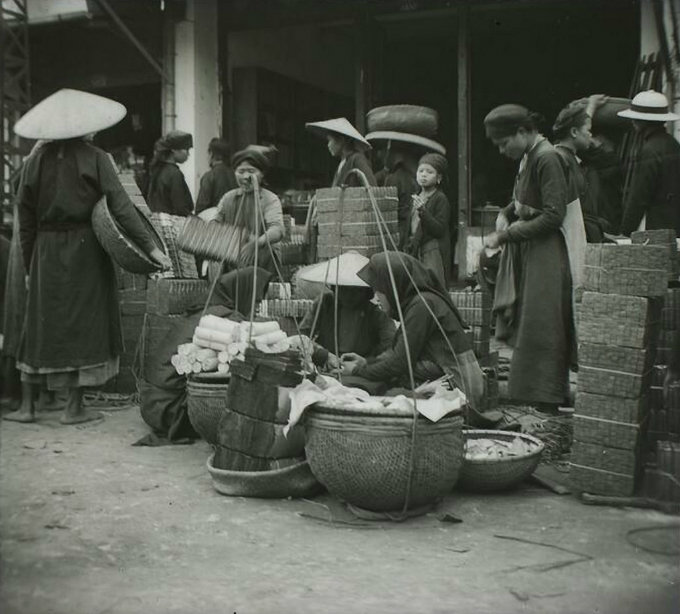 A woman were selling votive paper offerings. The practice of burning them during Tet symbolize how family members continue to remember and care for the deceased, as well as the gods and spirits.