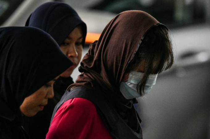 Vietnamese national Doan Thi Huong (R-face covered) is escorted by Malaysian police for another appearance at court in Shah Alam, outside Kuala Lumpur, on February 22, 2018 for her alleged role in the assassination of Kim Jong-Nam, the half-brother of North Korean leader Kim Jong-Un. Photo by AFP