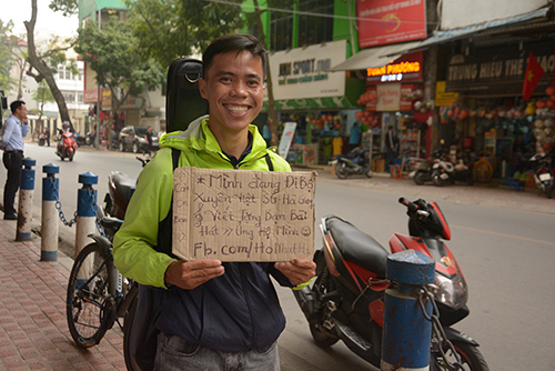 Ho Nhat Ha with a sign that says: Im walking across Vietnam. Would be happy to write you a song. Please support me! Photo provided by Ho Nhat Ha.