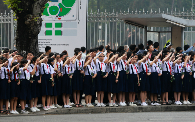 Students salute along the street outside the palace as his coffin leaves.