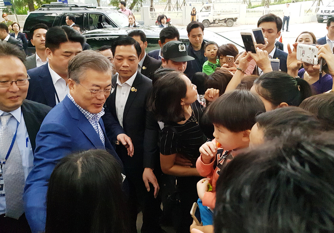 Moon takes photos with a group of South Korean people outside the restaurant. A woman said she never had a chance to see him in person in South Korea.
