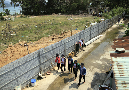 A group of girls walk pass the 3-km metal fence that block locals in Da Nang City from the sea area of Nam O fishing village. Photo by VnExpress/Nguyen Dong