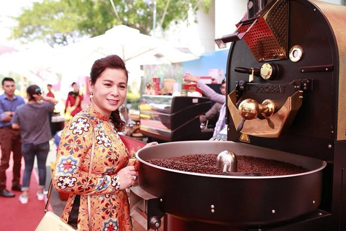 Le Hoang Diep Thao stands next to a coffee grinder in a King Coffee launch event. Photo courtesy of Le Hoang Diep Thaos official Facebook fanpage.