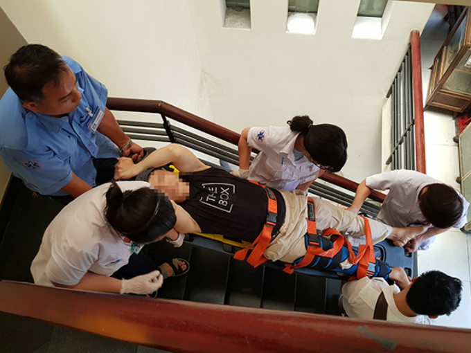Responders and a driver carry a patient downstairs after he broke his leg. Photo by VnExpress/Le Phuong