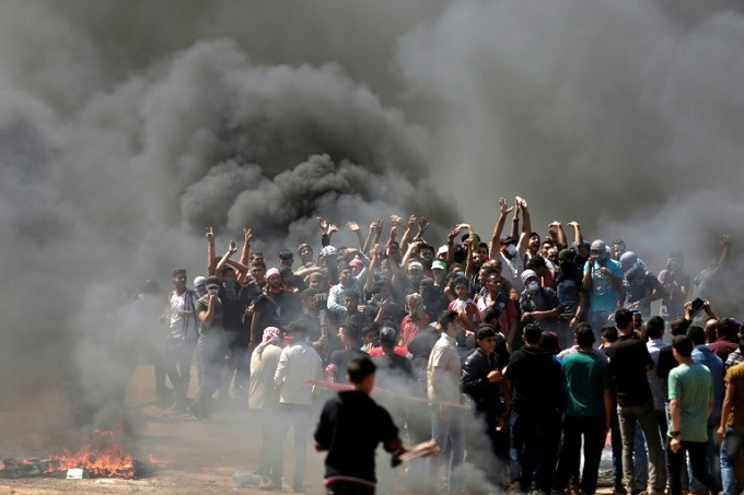 Palestinian demonstrators burn tyres near the Gaza-Israel border on May 14, 2018. Photo byAFP/Mahmud Hams