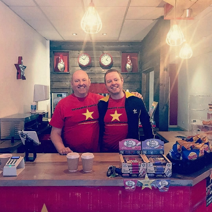 The Smalls brothers in their Vietnamese coffee shop in Belfast, which has two clocks showing local and Hanoi time. Photo: VCC