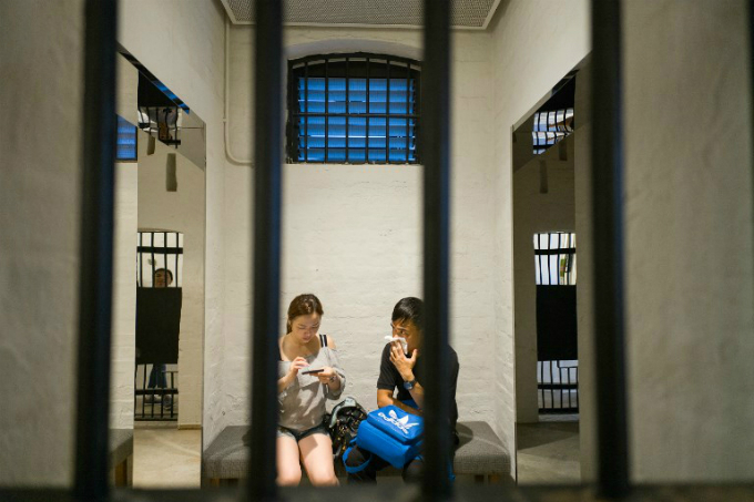 People sit in a cell as they visit Victoria Prison, a former colonial prison and police station colloquially known as Tai Kwun. Photo by AFP/Anthony Wallace
