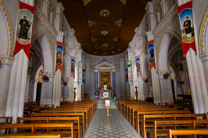 The churchs interior embraces Romanesque traditional features,  including clustered columns, stained glass windows, and pointed arches.
