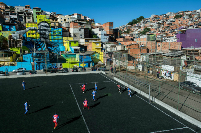 Residents play football in a field crammed between buildings of the Perus neighbourhood of Sao Paulo, Brazil. Photo by AFP
