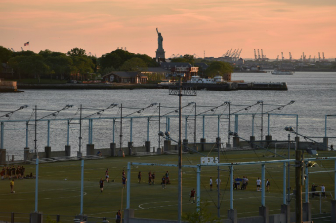 People play a football at Brooklyn Bridge Park in New York City, against the background of the Statue of Liberty. Photo by AFP