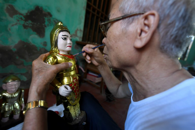 Vietnamese craftsman Pham Viet Duc, 76, putting finishing touches on a water puppet at a workshop in Thai Binh province. Photo by AFP/Nhac Nguyen