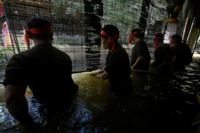 Vietnamese puppeteers controlling water puppets from behind a bamboo screen in a pool during a performance at the Museum of Ethnography in Hanoi. Photo by AFP/Nhac Nguyen