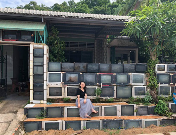 A traveler takes picture in front of the fence made of old TVs. Photo by Tien Thanh