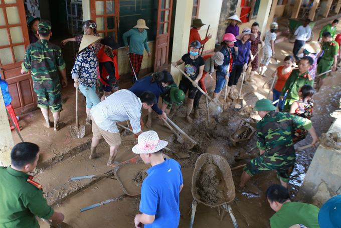 Soldiers and civilian volunteers worked together with local residents to rake the mud inside the schoolyard so that students can get back to classes soon.