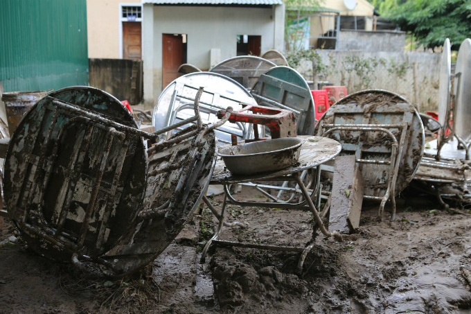Tables, chairs and school equipment were covered in sludge and people stacked them outside to be cleaned and then left in thế sun to dry.