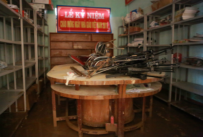 A schoolroom containing documents and records was flooded by two meters and its no easy task for volunteers to clear away the mess of mud on the ground.
