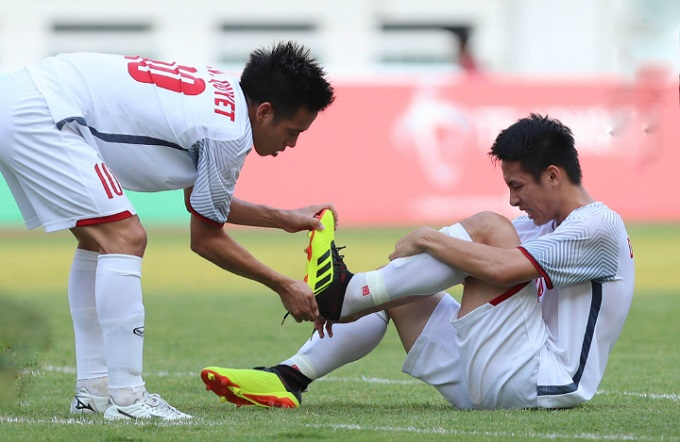 Nguyen Van Quyet (L), Vietnams captain, helps midfielder Do Hung Dung remove his shoe during the game against Japan at Asian Games 2018 on August 19 in Indonesia. Dung has been ruled out of the tournament by doctors, who say he might have to return to Vietnam for surgery. Photo by VnExpress/Duc Dong