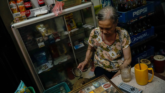 At the alley entrance, Giao has opened a street café in front of her house. She usually turns on just one light bulb to save electricity. Her children are not too happy with this arrangement, since she is old now and her eyesight is poor.