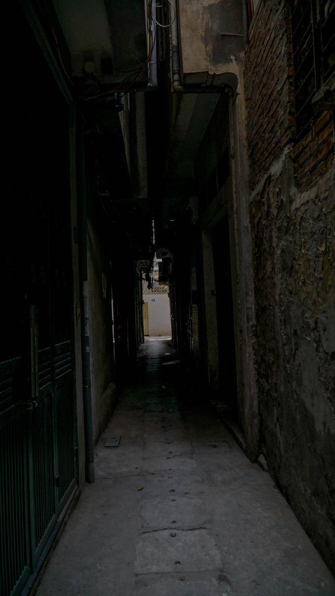 Behind Giaos house, Alley 87/1 on the same street is less roomy and more gloomy. In this 100-meter long alley reside 16 households. A single ray of sunlight shines into the alley in front of Nguyen Thi Saus house. In other places, people standing a few steps away can barely see each others face.