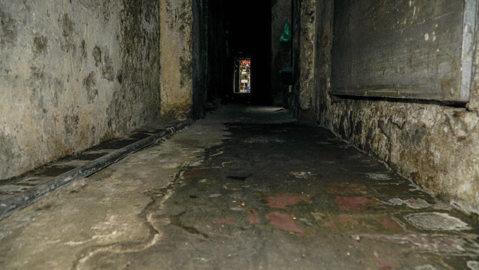 At midday, Alley 53 on Hang Buom Street is completely in the shade. Footsteps and shouts echo here. Except for late in the night, houses keep their lights on all the time.