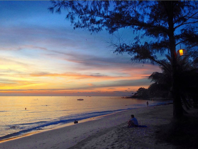A tourist sits on the smooth sands of Ong Lang Beach in Phu Quoc at sunset. Photo by Leonievits
