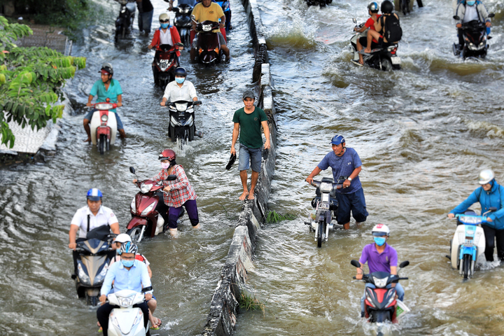 Life goes on as high tide floods Saigon without fail