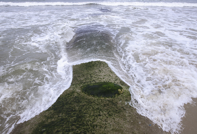 Visitors sunbathe on embankment as erosion ravages central Vietnam beach