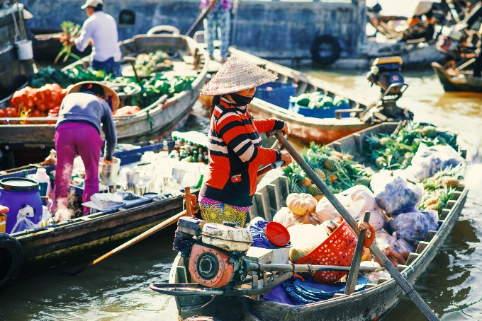 Vendors selling fruits, vegetables, snacks and soft drinks at a floating market in Can Tho City. Photo by Shutterstock/Nevskii Dmitrii
