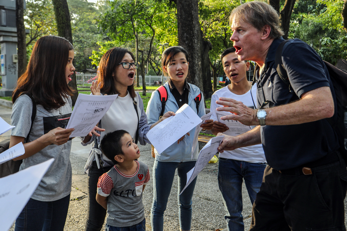 A foreign teacher is teaching English to Vietnamese students of an English centerat an open park in HCMC which takes place every Sunday afternoon. Photo by VnExpress/ Thanh Nguyen.