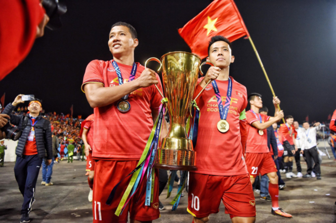 Nguyen Anh Duc (L) and Nguyen Van Quyet carry the AFF Cup 2018 trophy. Photo by Duc Dong/VnExpress.