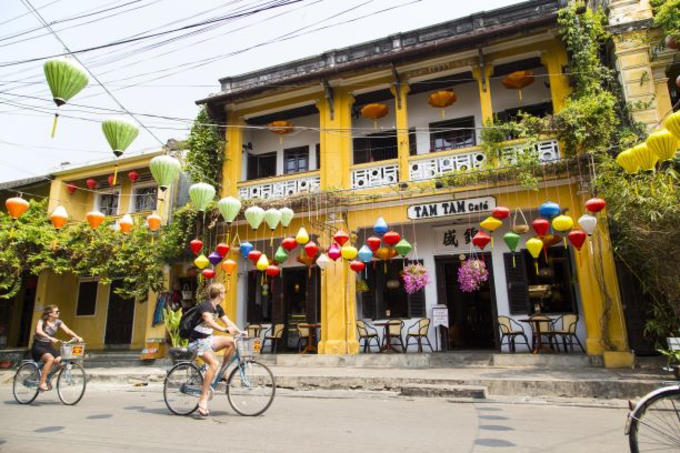 Foreign tourists ridebicyclespasttypical yellow houses of Hoi An. Photo by Shutterstocks/minhtan