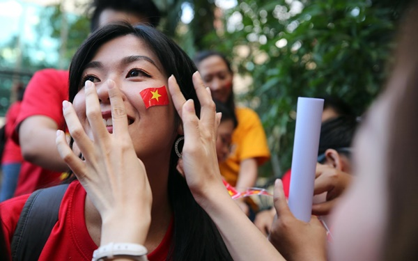 A Vietnamese fan puts on a national flag.