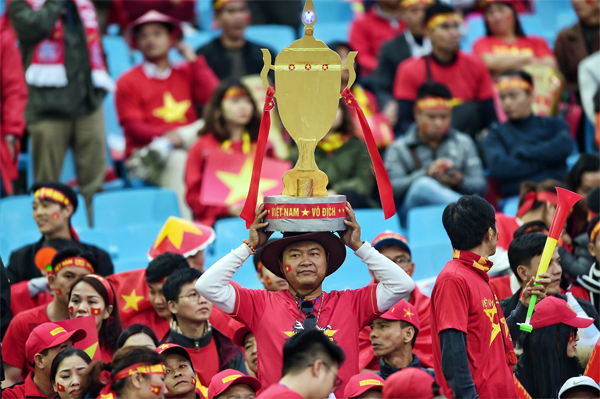 A Vietnamese fan carries a replica of the AFF Cup at My Dinh Stadium in Hanoi. Photo by VnExpress/Giang Huy